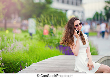 Happy girl talk by smartphone outdoors in the park. Young attractive woman with mobile phone outdoors enjoying holidays travel destination in tourism and exploring concept