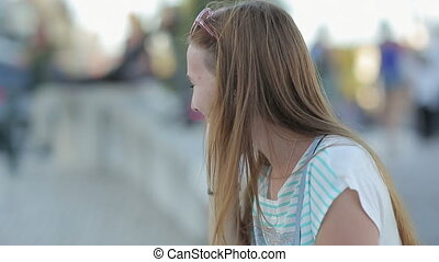 Happy girl talking by smart phone in a city embankment sitting