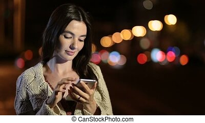 Happy girl texting message on phone in night city