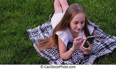 Happy girl typing sms by phone lies on grass in the park -...