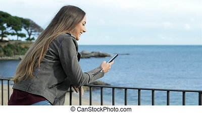 Happy girl using a smart phone in a balcony with the sea in...