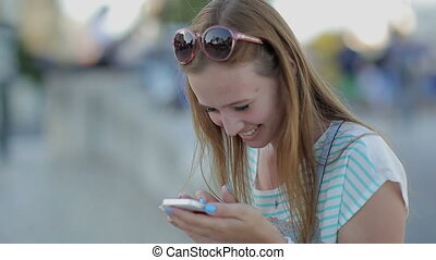 Happy girl using a smart phone in a city embankment sitting