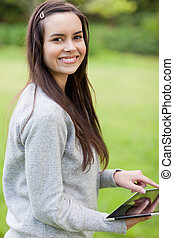 Happy girl using her tablet pc while standing in a park and looking at the camera