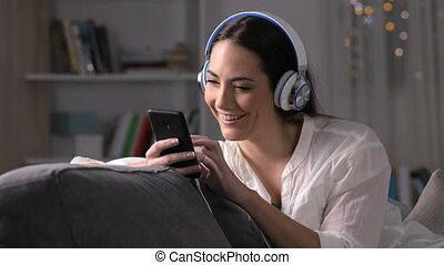 Happy girl using phone to listen to music at home sitting on...