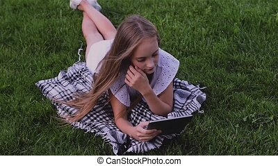 Happy girl using tablet pc lies on grass in the park