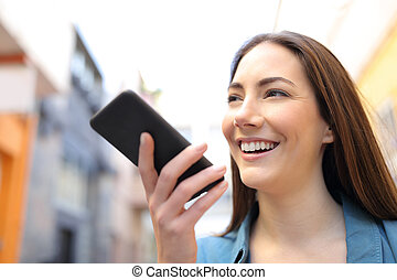 Happy girl using voice recognition app on smart phone