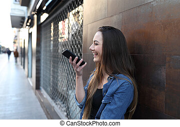 Happy girl using voice recognition on smart phone