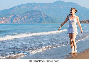 Happy girl walking barefoot on the beach