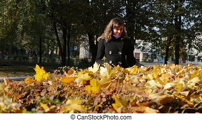 Happy girl walking in autumn park and collects yellow fallen leaves.