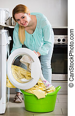 Happy girl washing bed linen and towels - Positive female ...