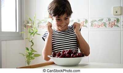 Happy girl watching and eating a big bowl of cherries. -...