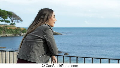 Happy girl watching the sea from a balcony