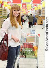Happy girl wearing white shirt and cart with food; shallow depth of field