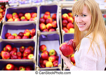 Happy girl wearing white shirt chooses apples in store; shallow depth of field