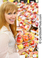 Happy girl wearing white shirt keeps packed apples in store; shallow depth of field