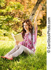 Happy Girl with a book in the park