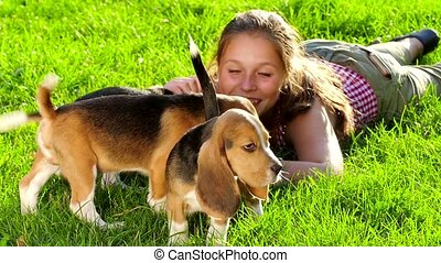 happy girl with a dog beagle playing on nature. Close up