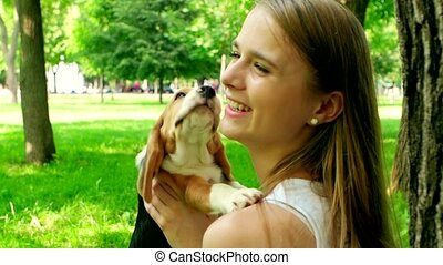 happy girl with a dog beagle playing on nature. Slow motion