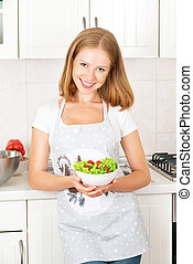 happy girl with a vegetable salad in the kitchen