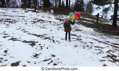Happy girl with colorful umbrella in the winter landscape