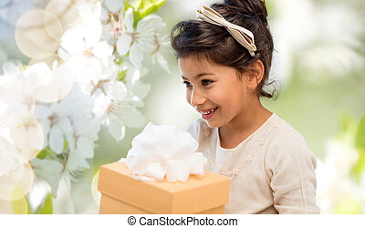 happy girl with gift box over cherry blossom