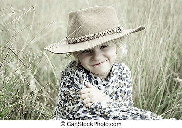 happy girl with hat in autumn meadow