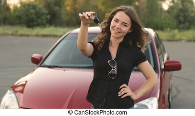 Happy girl with key in hand from new car