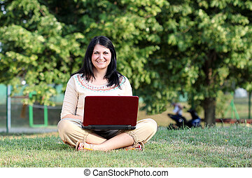 happy girl with laptop sitting on grass