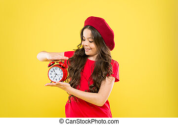 happy girl with long curly hair in beret. child with alarm clock. Timeless fashion. parisian child on yellow. beauty hairdresser. little girl in french style hat. Girl shows the time on the clock