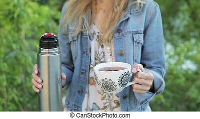 Happy girl with long hair holds a cup of tea or coffee in hands against the blurred nature background. Pretty woman in jeans jacket holds a thermos with beverage.