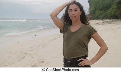 Happy girl with long hair posing on beach in Bali