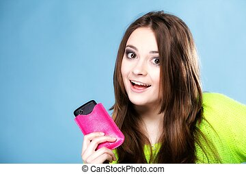 Happy girl young woman with mobile phone smartphone in pink cover studio shot blue background