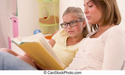 happy girl with mother reading book at home - people, family...