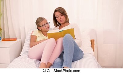 happy girl with mother reading book at home