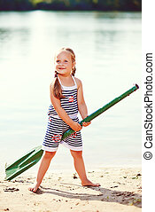 happy girl with paddle at beach. toned image