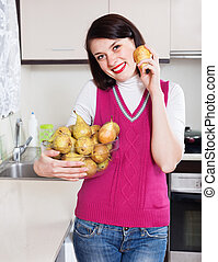 Happy girl with pears in kitchen
