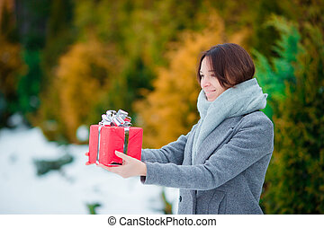 Happy girl with red christmas box gift in winter day outdoors