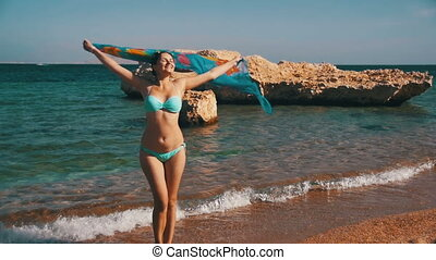 Happy Girl with Scarf Walking on the Summer Beach in Red Sea. Slow Motion