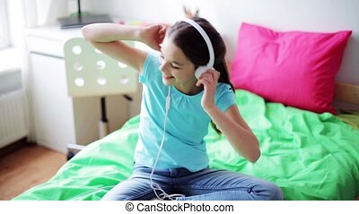 happy girl with smartphone and headphones at home