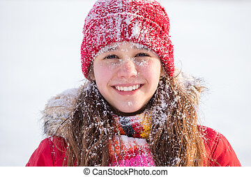 Happy girl with snow on face at winter landscape