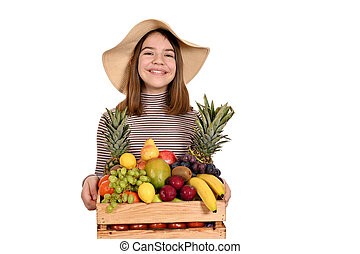 happy girl with straw hat holds a wooden crate with fruit