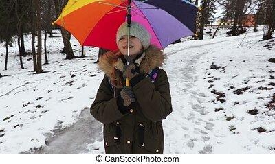 Happy girl with umbrella in winter
