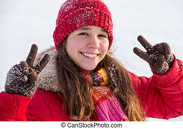 Happy girl with victory sign at winter landscape