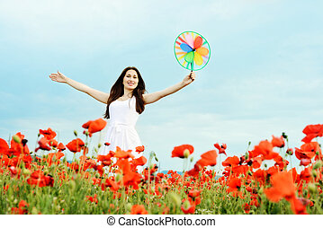 happy girl with windmill in field