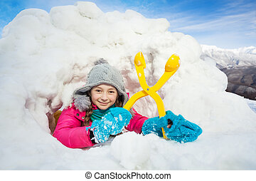 Happy girl with yellow snowmaker in the snow igloo - Happy...