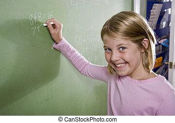 Happy girl writing math on blackboard in class