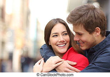 Happy girlfriend with perfect teeth being embraced