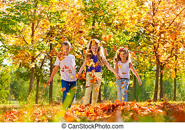 Happy girls and boy playing in the forest together