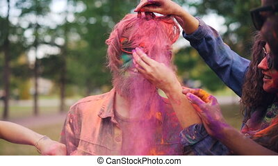 Happy girls and guys are painting friend with bright colorful powder at Holi festival touching his face, hair and beard, young man in sunglasses is laughing.