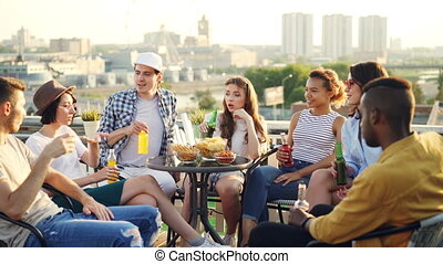 Happy girls and guys students are having rooftop party...